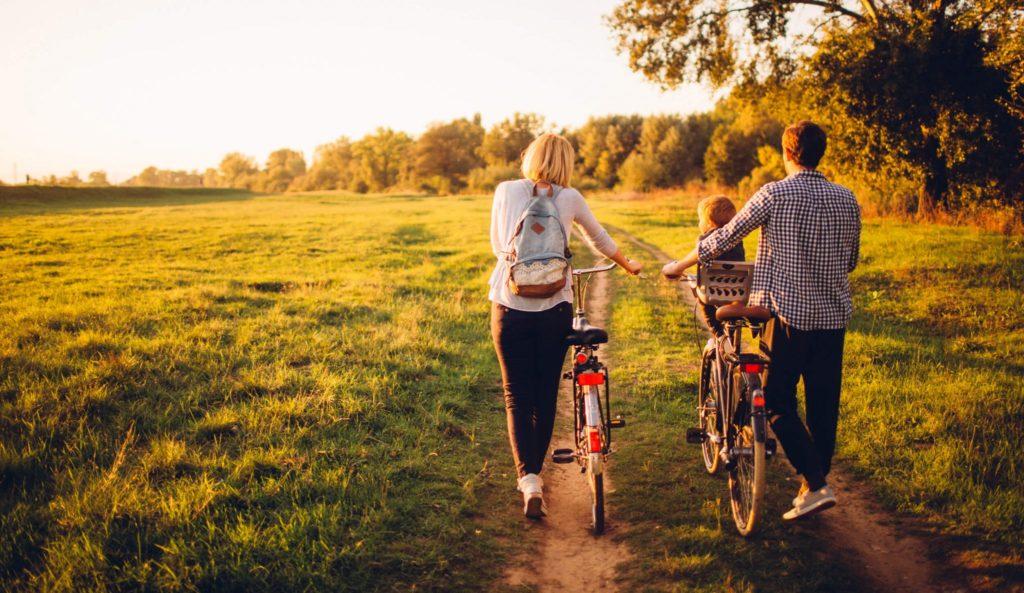 Människor som går på en äng med sitt barn och cykel